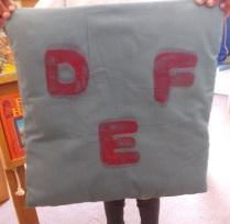 Druk die alfabet op ou kussings met sponsletters en lapverf.